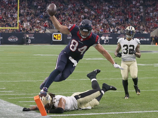 Ryan Griffin #84 of the Houston Texans jumps and lands on the pylon to score a touchdown while Vinnie Sunseri #43 of the New Orleans Saints defends on the play on November 29, 2015