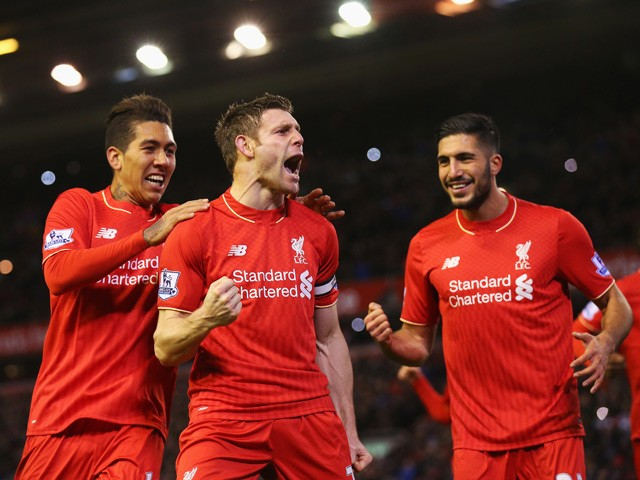 James Milner of Liverpool (C) celebrates with Roberto Firmino (L) and Emre Can (R) as he scores their first goal from a penalty during the Barclays Premier League match between Liverpool and Swansea City at Anfield on November 29, 2015