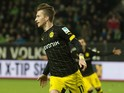 Dortmund's forward Marco Reus (L) reacts after scoring the opening goal passed Wolfsburg's Swiss goalkeeper Diego Benaglio (C ) during the German first division Bundesliga football match Wolfsburg vs Dortmund in Wolfsburg on December 5, 2015.