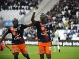 Montpelliers Chadian forward Casimir Ninga (R) celebrates after scoring a goal during the French L1 football match Olympique de Marseille against Montpellier on December 6, 2015 at Velodrome Stadium in Marseille, southern France.