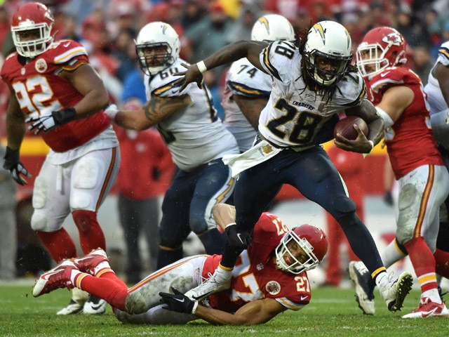 Melvin Gordon #28 of the San Diego Chargers runs through the tackle attempt of Tyvon Branch #27 of the Kansas City Chiefs at Arrowhead Stadium during the third quarter of the game on December 13, 2015