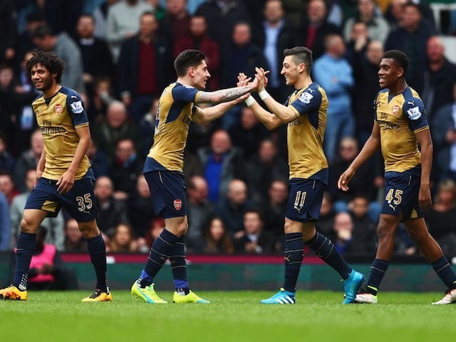 Mesut Ozil celebrates scoring with Hector Bellerin during the Premier League game between West Ham United and Arsenal on April 9, 2016