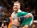 Conor McGregor celebrates winning a fight with his Irish flag and belt