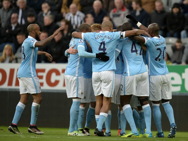 Manchester City players huddle around Sergio Aguero to celebrate the opening goal in their Premier League clash with Newcastle United on April 19, 2016