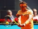 Rafael Nadal plays a backhand against Andrey Kuznetsov in their second-round match during day four of the Mutua Madrid Open on May 3, 2016