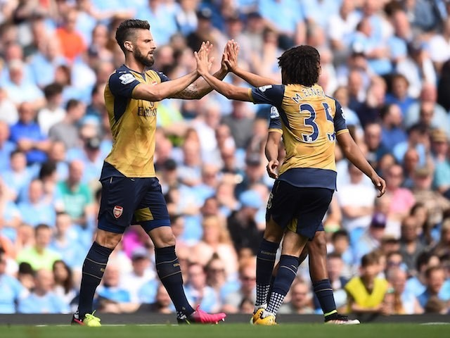 Olivier Giroud celebrates with Mohamed Elneny during the Premier League game between Manchester City and Arsenal on May 8, 2016