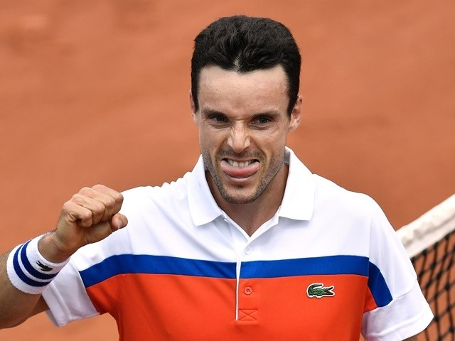Roberto Bautista-Agut eats a sausage after winning his men's second-round match against Paul-Henri Mathieu at the French Open on May 26, 2016
