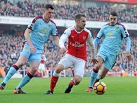 Aaron Ramsey is pursued by Matthew Lowton and Michael Keane during the Premier League game between Arsenal and Burnley on January 22, 2017