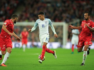 Malta players chase after Jesse Lingard in a match between England and Malta at Wembley